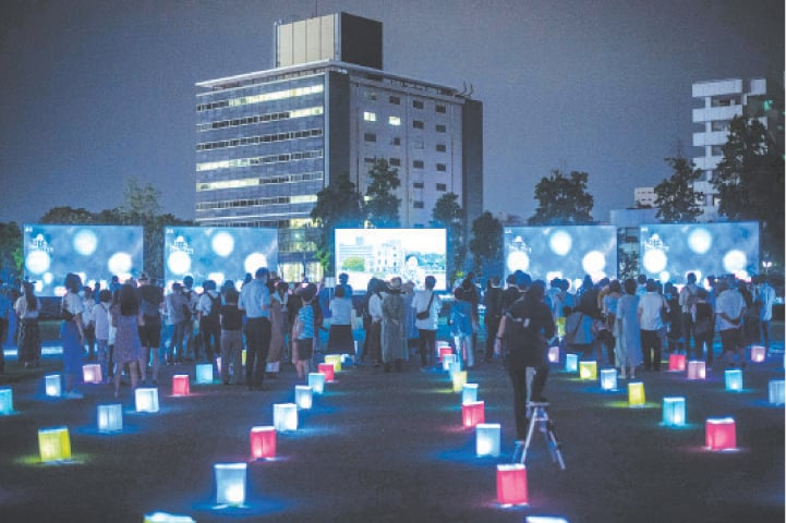 Hiroshima (Japan): Visitors watch a screen (back centre) displaying virtual lanterns as paper lanterns are placed to mark the 75th anniversary of the atomic bombing, at a park on Thursday. The coronavirus pandemic forced the government to scale back ceremonies to commemorate the victims.—AFP