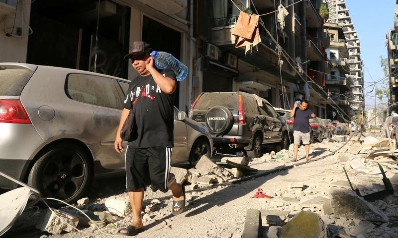 Men carrying bottles of water walk past damaged buildings and vehicles near the site of Tuesday's blast in Beirut's port area, August 5, 2020. — Reuters