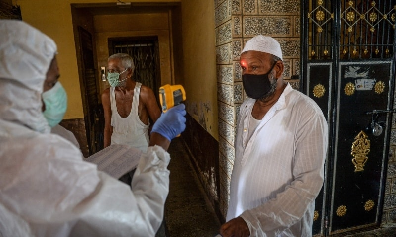 A health worker checks the body temperature of a resident during a door-to-door coronavirus screening campaign at a building in Dharavi slum area in Mumbai on August 7. —  AFP