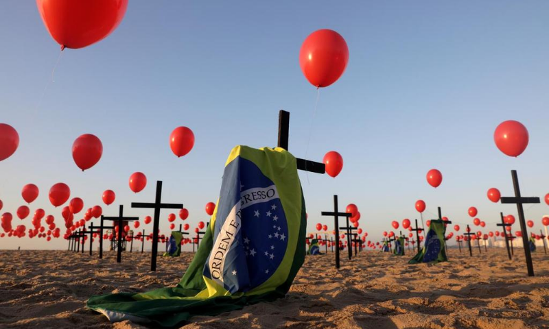 Crosses, balloons and Brazilian flags are seen at Copacabana beach, placed by members of the NGO Rio de Paz in tribute to the 100,000 victims of the coronavirus  in the country, in Rio de Janeiro, Brazil on Saturday. — Reuters