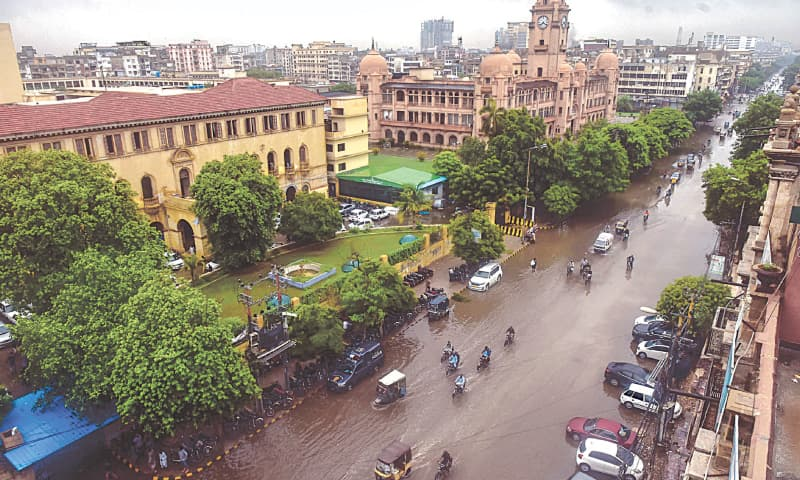 VEHICLES wade through rainwater on MA Jinnah Road on Saturday in front of the KMC head office.—Fahim Siddiqi/White Star