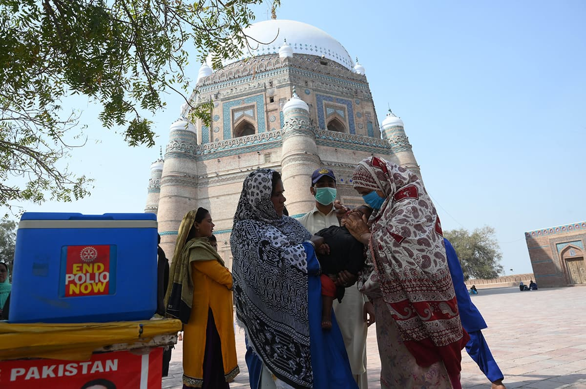 A Lady Health Worker administers polio drops to a child in Multan while wearing a mask | Arif Ali/White Star