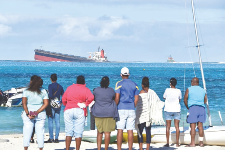 Bystanders look at MV Wakashio bulk carrier that had run aground and from which oil is leaking near Blue Bay Marine Park in south-east Mauritius.—AFP