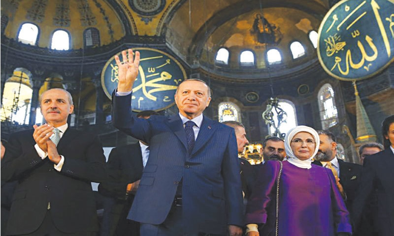 Turkey President Recep Tayyip Erdogan accompanied by his wife, Emine, waves to supporters inside the Hagia Sophia, 2018   AP