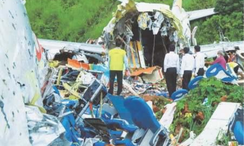 KARIPUR (India): Officials inspecting on Saturday the wreckage of the plane that crashed after skidding off the airport near here. — AFP