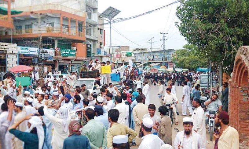 Protesters passing through a road in Kohat on Sunday. — Dawn