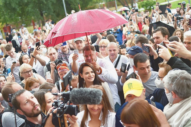 MINSK: Voters and journalists surround joint opposition candidate Svetlana Tikhanovskaya (centre) as she arrives to cast her ballot at a polling station on Sunday.—AFP