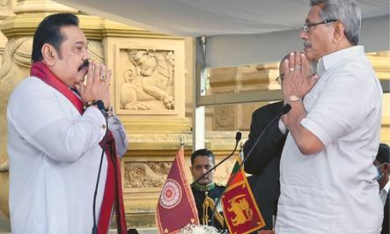 COLOMBO: Sri Lakan President Gotabaya Rajapaksa (right) prays before he swears in his elder brother Mahinda as prime minister at a Buddhist temple on Sunday. — AFP
