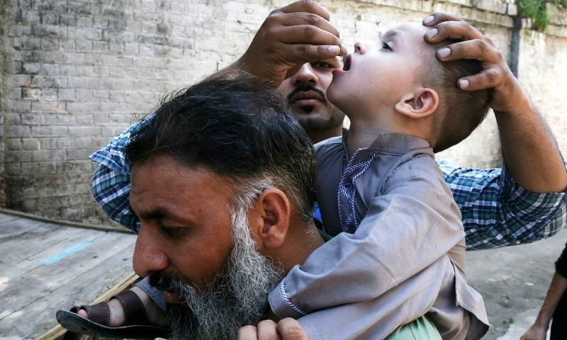 صحت رضا کار بچے کو پولیو کے قطرے پلاتے ہوئے—فائل فوٹو: اے پی