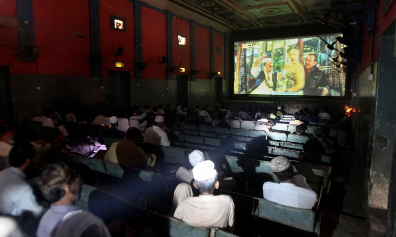 People watch a movie at a cinema following an ease in Covid-19 restrictions in Peshawar, Monday, Aug 10. — AP