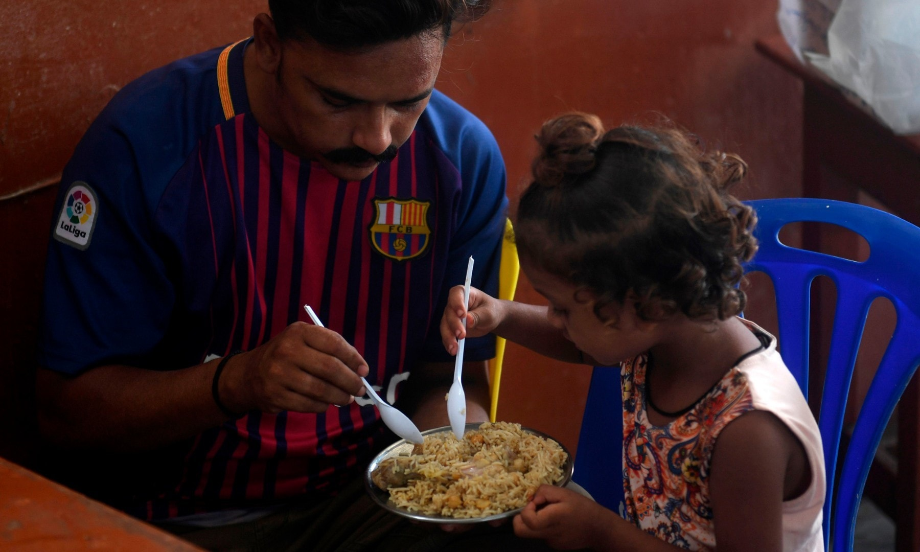 A man eats with his daughter at a restaurant in Karachi on August 10 after the government announced it would be lifting most of the country's remaining coronavirus restrictions. — AFP