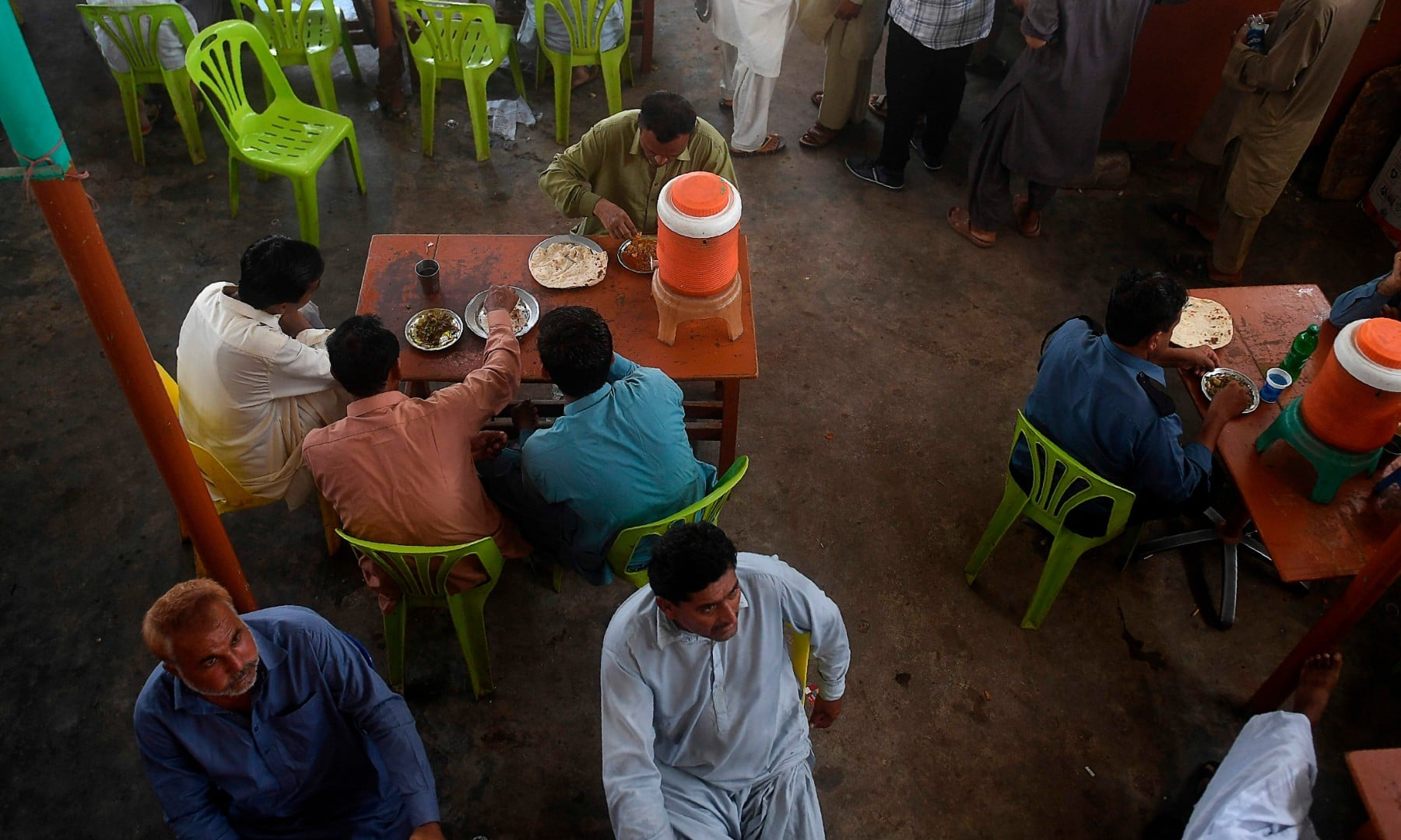 People eat at a restaurant in Karachi on August 10 after the government announced it would be lifting most of the country's remaining coronavirus restrictions. — AFP
