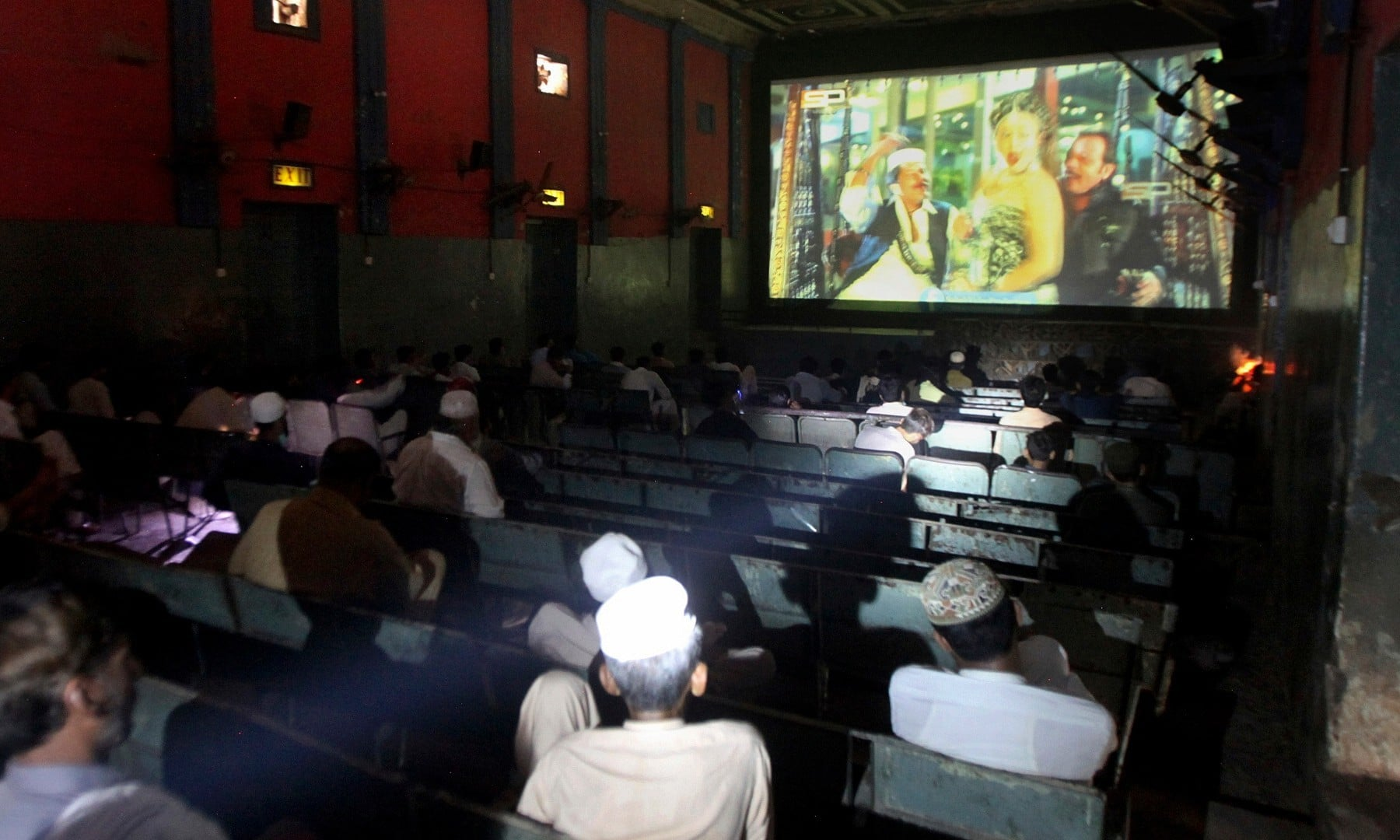 People watch a movie at a cinema following an ease in restrictions that had been imposed to help control the coronavirus in Peshawar on August 10. — AP