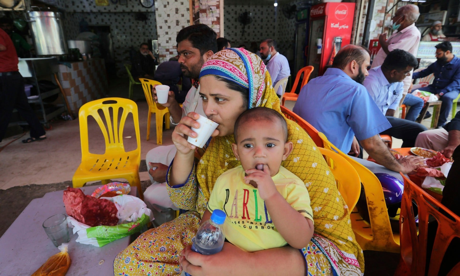 People eat at a restaurant following an ease in restrictions that had been imposed to help control the coronavirus in Karachi on August 10. — AP
