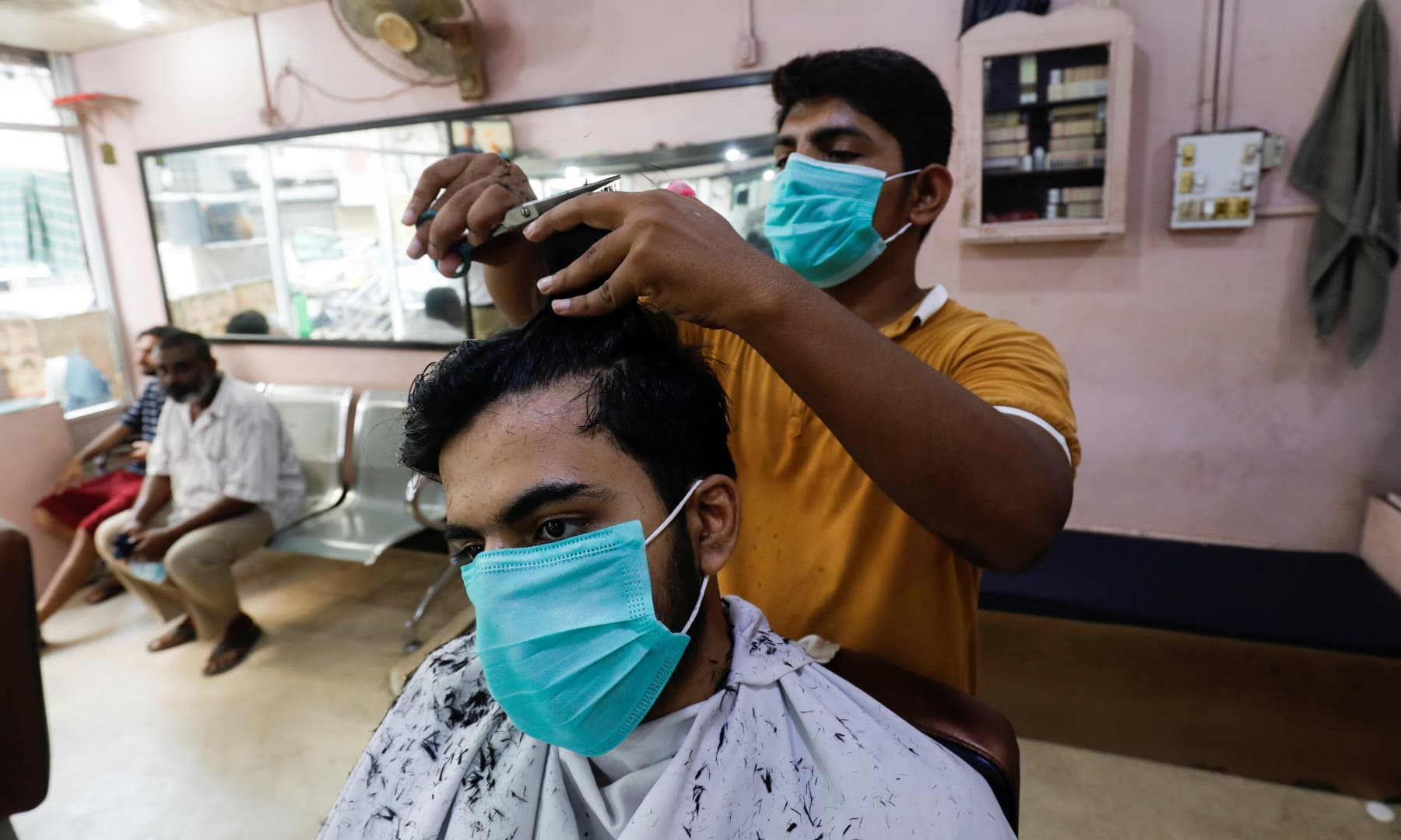 A man wears a protective mask as he gets a haircut at a barbershop in Karachi, August 10. — Reuters