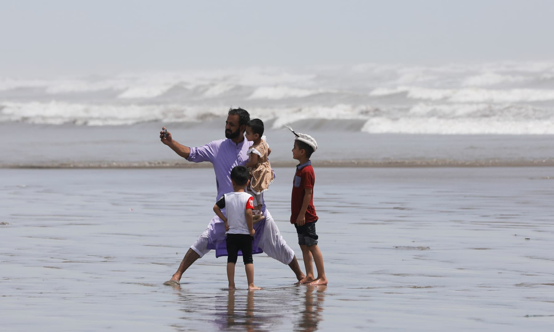 A man takes a selfie with his children while they visit Clifton beach in Karachi, August 10. — Reuters
