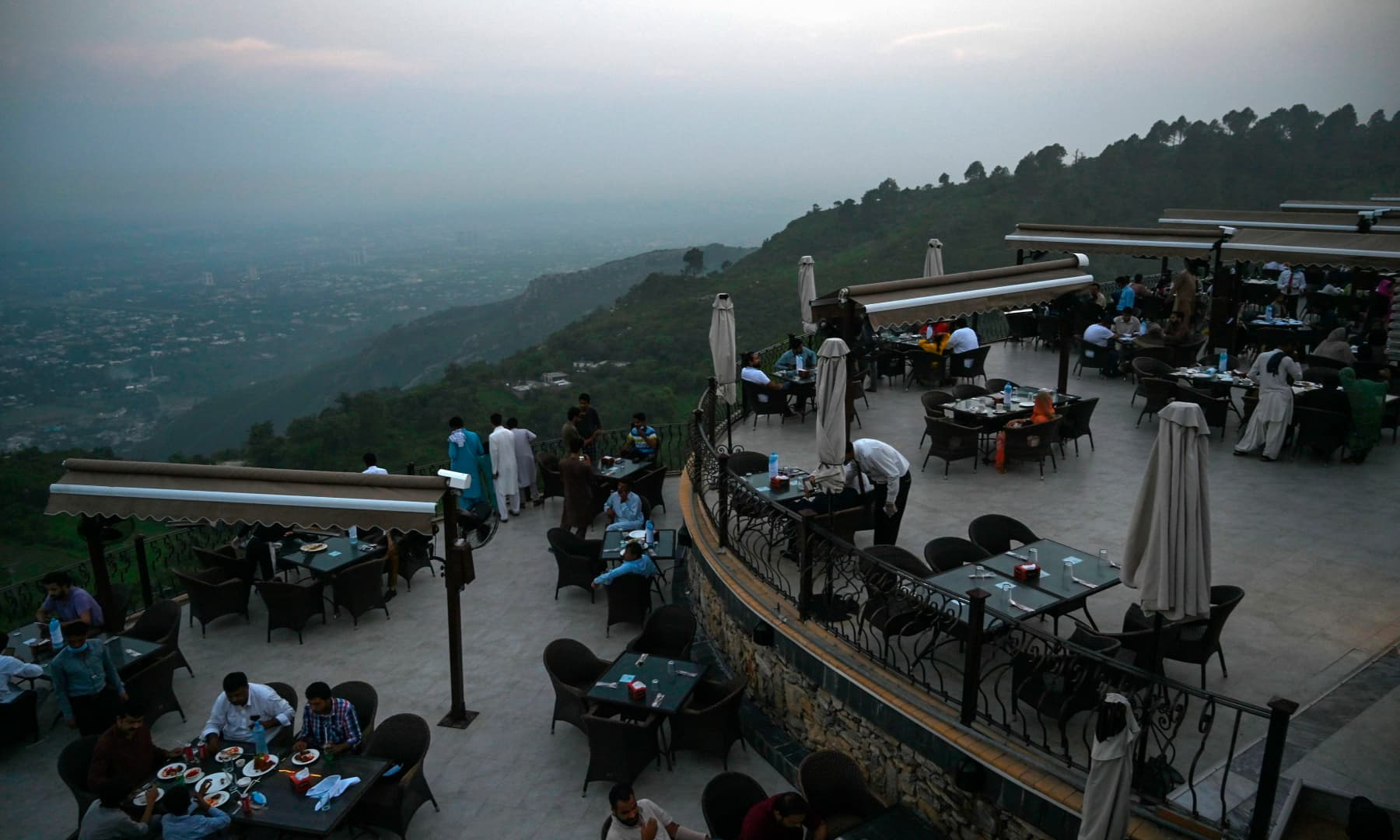 People eat at a rooftop restaurant on Margalla Hills in Islamabad on August 10, after government announced it would be lifting most of the country's remaining coronavirus restrictions. — AFP
