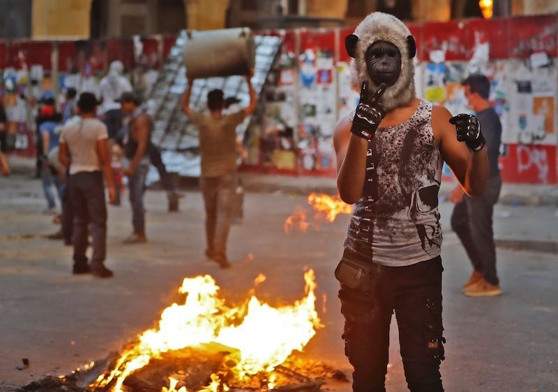 A Lebanese protester, wearing a monkey mask, gestures next to burning fire amid clashes with security forces in the vicinity of the parliament in central Beirut on August 10, 2020. — AFP