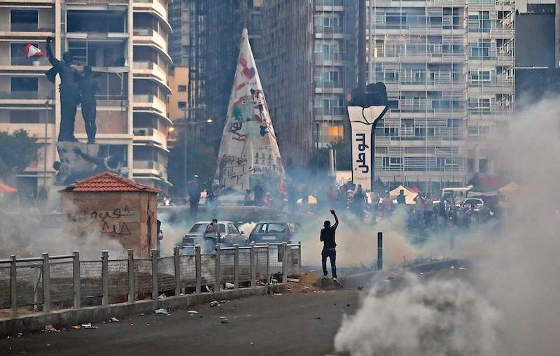 Lebanese protesters, enraged by a deadly explosion, clash with security forces at Martyrs' Square in Beirut on August 10, 2020. — AFP