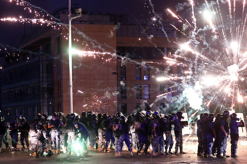 Fireworks are set off in front of police officers during anti-government protests that have been ignited by a massive explosion in Beirut, Lebanon, on August 10, 2020. — Reuters