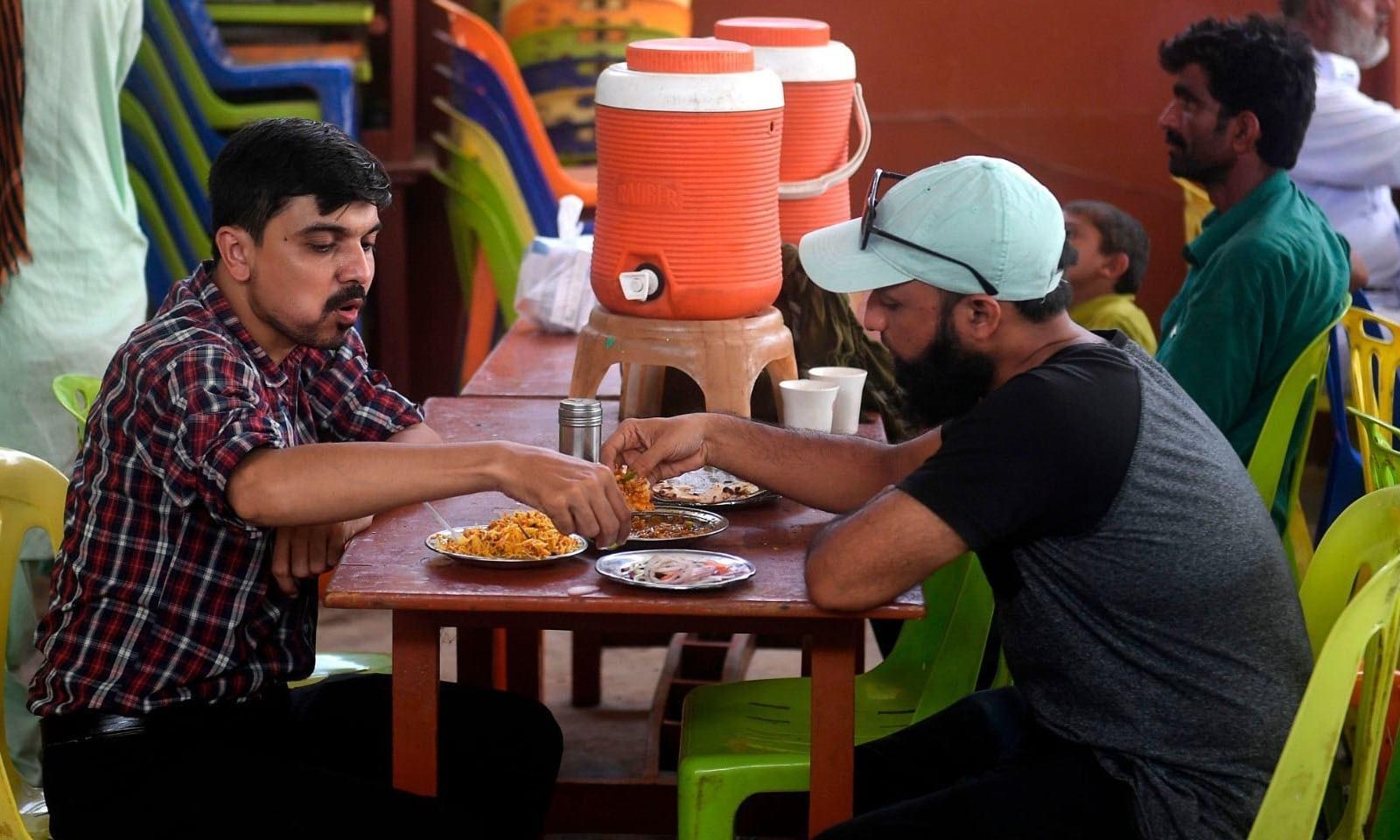 کراچی کے ایک مقامی ہوٹل میں  شہری کھانا کھا رہے ہیں— فوٹو: اے ایف پی