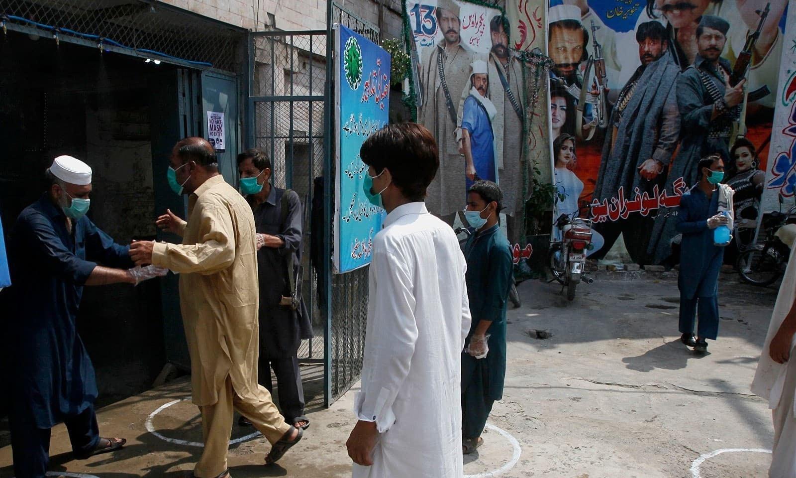 پشاور میں لوگ سینما میں داخل ہونے کیلئے سماجی فاصلہ برقرار رکھے ہوئے ہیں —فوٹو: اے پی