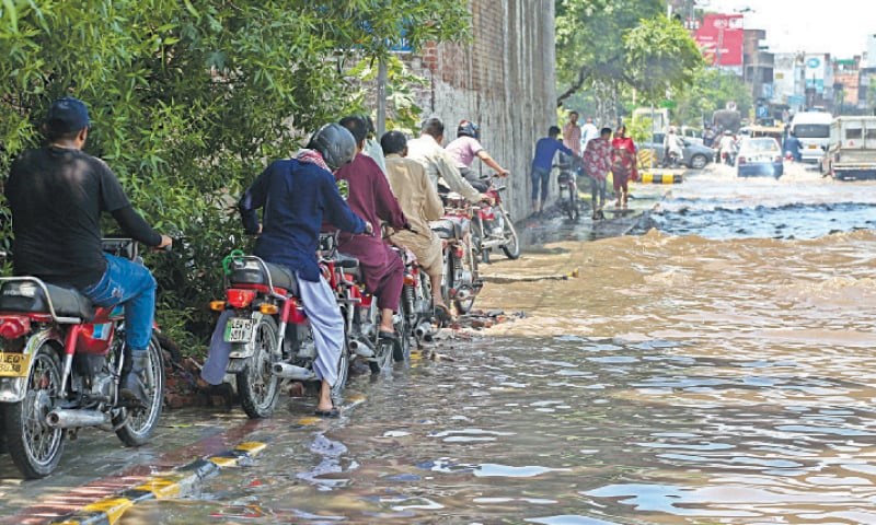 Motorcyclists use footpath as the Allama Iqbal Road is flooded after heavy rain. — White Star / Aun Jafri