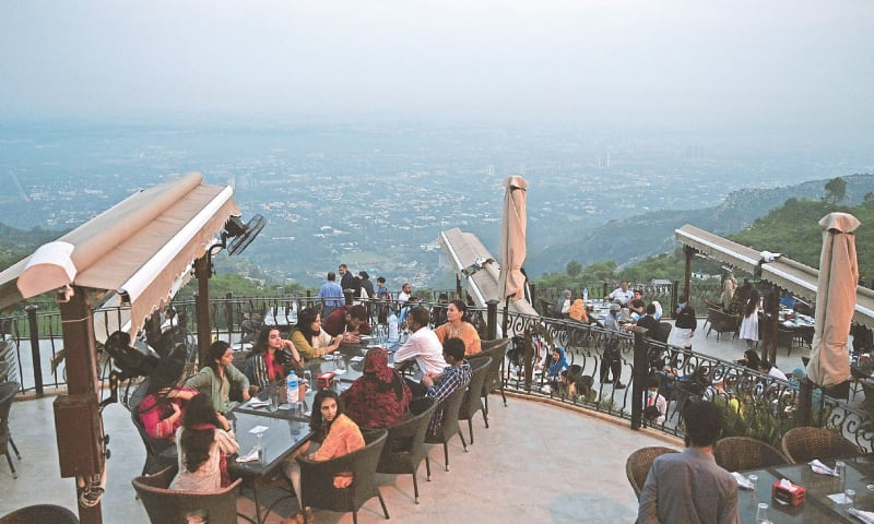 ISLAMABAD: People wait for food at a restaurant on Margalla Hills on Monday after the government  announced it would be lifting most of the coronavirus restrictions after seeing new cases drop for several weeks.—AFP