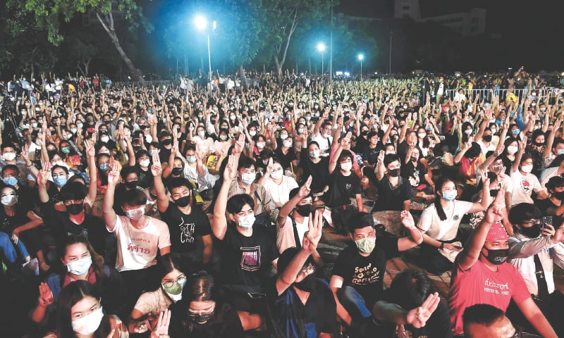 Bangkok: Protesters flash the Hunger Games salute during a pro-democracy rally at Thammasat University on Monday. — AFP