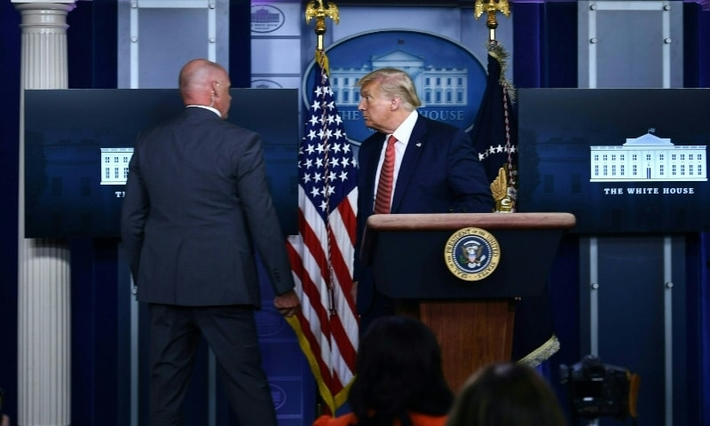 US President Donald Trump is being removed by a member of the secret service from the Brady Briefing Room of the White House in Washington, DC, on August 10, 2020. — AFP