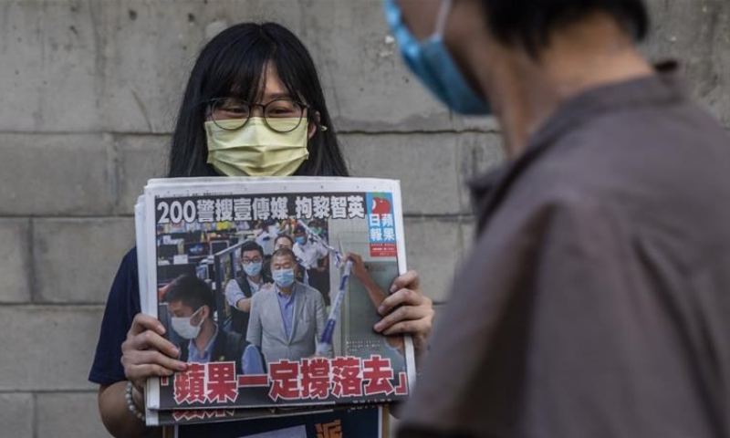 Volunteer hands out copies of Apple Daily in Hong Kong on August 11. — AFP