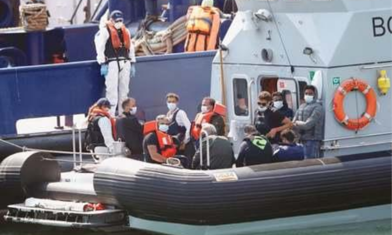 DOVER (United Kingdom): Migrants are being brought to Dover harbour by security personnel on Tuesday. — Reuters