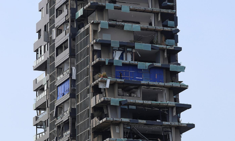 A man is seen on the balcony of a destroyed building, following a massive explosion, in Beirut, Lebanon. — Reuters