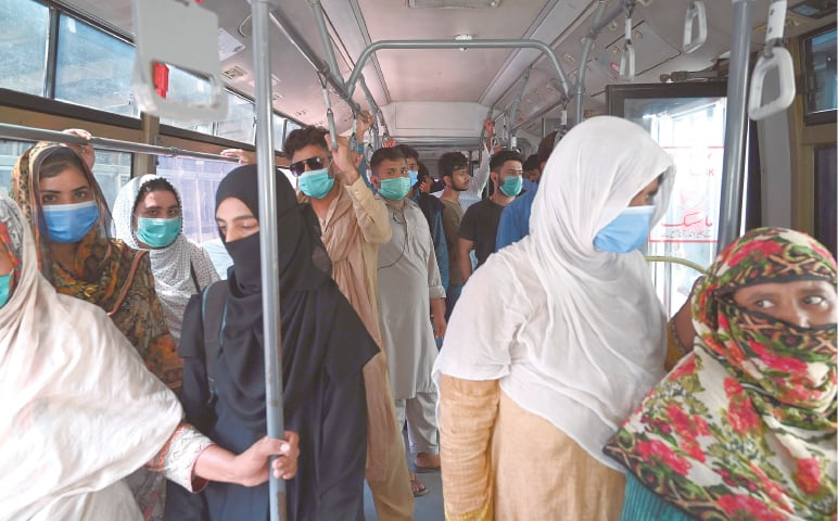 LAHORE: Commuters wearing face masks travel in a Metro bus on Wednesday after the government announced lifting most of the remaining coronavirus restrictions in wake of continuous drop in new cases. The bus resumed its operations after 140 days. — AFP