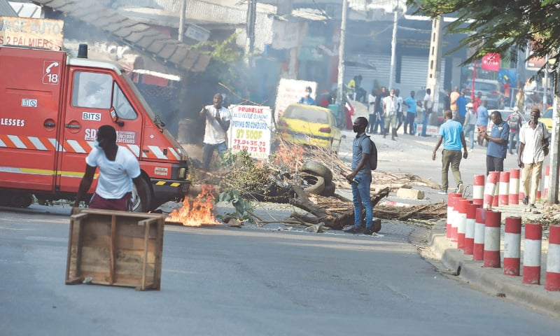 ABIDJAN: Young demonstrators burn barricades on the road to protest a decision by Ivory Coast President Alassane Ouattara to contest elections for a third term.—AFP