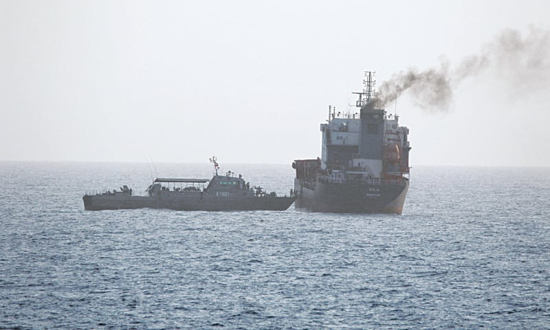 WASHINGTON: This picture released by the US Navy allegedly shows a ship of the Iranian Navy and members of the Iranian forces boarding a civilian tanker  in the Strait of Hormuz.—Reuters