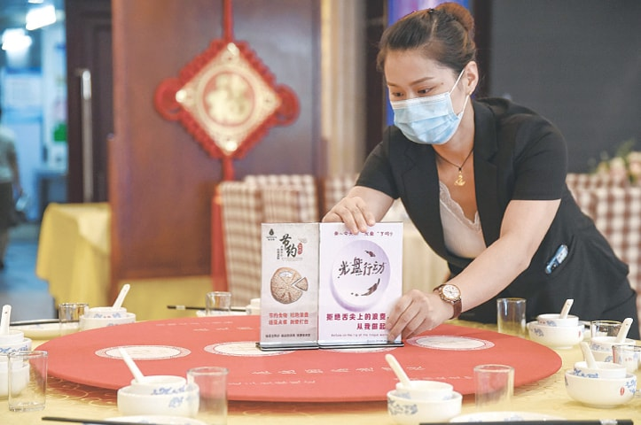 A staff member sets up signs encouraging people not to waste food at a restaurant in Handan in China's northern Hebei province on Thursday.—AFP