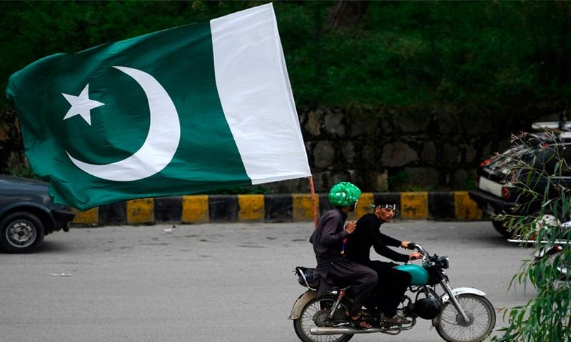 جشن آزادی کے موقع پر نوجوان موٹرسائیکل پر قومی پرچم اٹھائے ہوئے—فوٹو: اے ایف پی