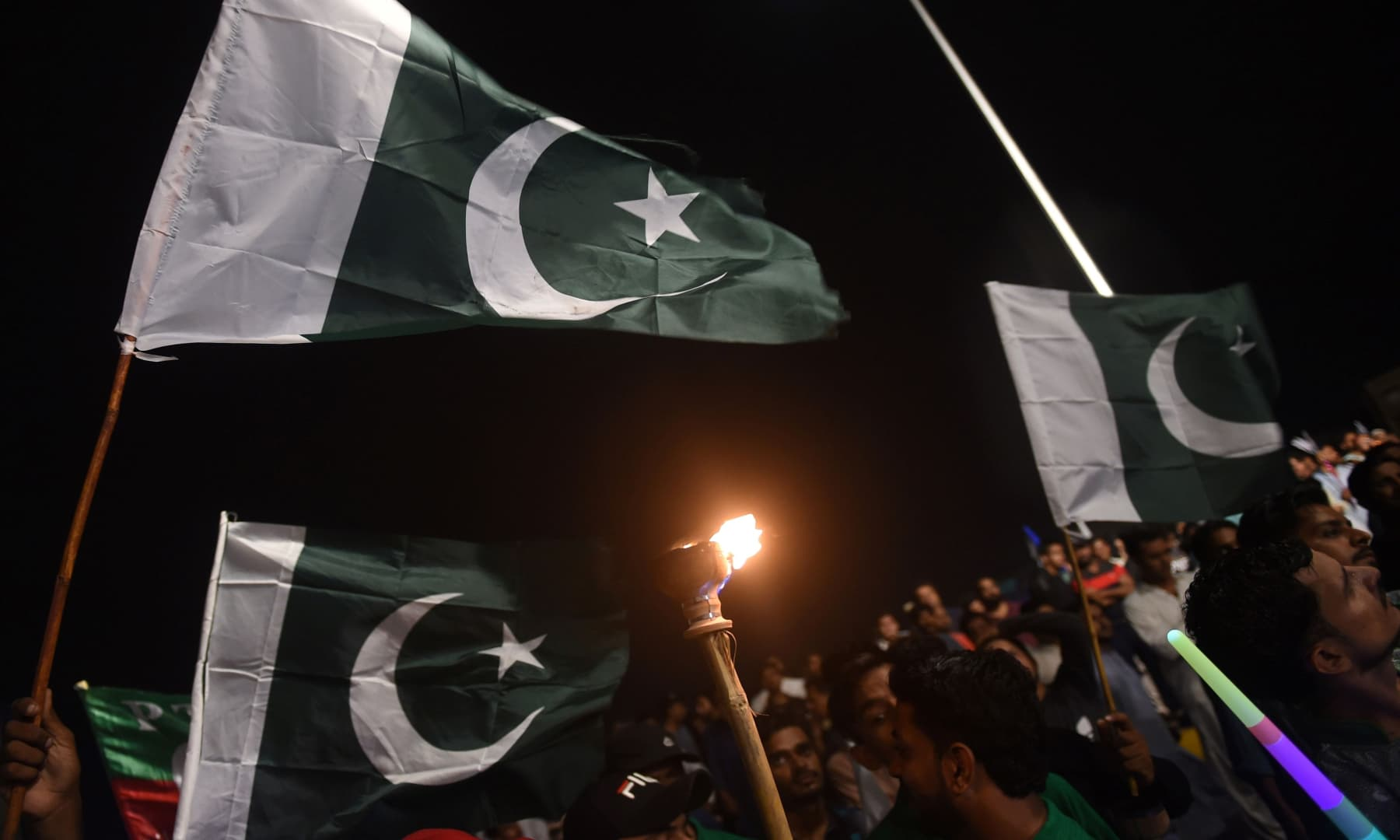 People hold national flags as they gather during Independence Day celebrations in Karachi on August 14. — AFP