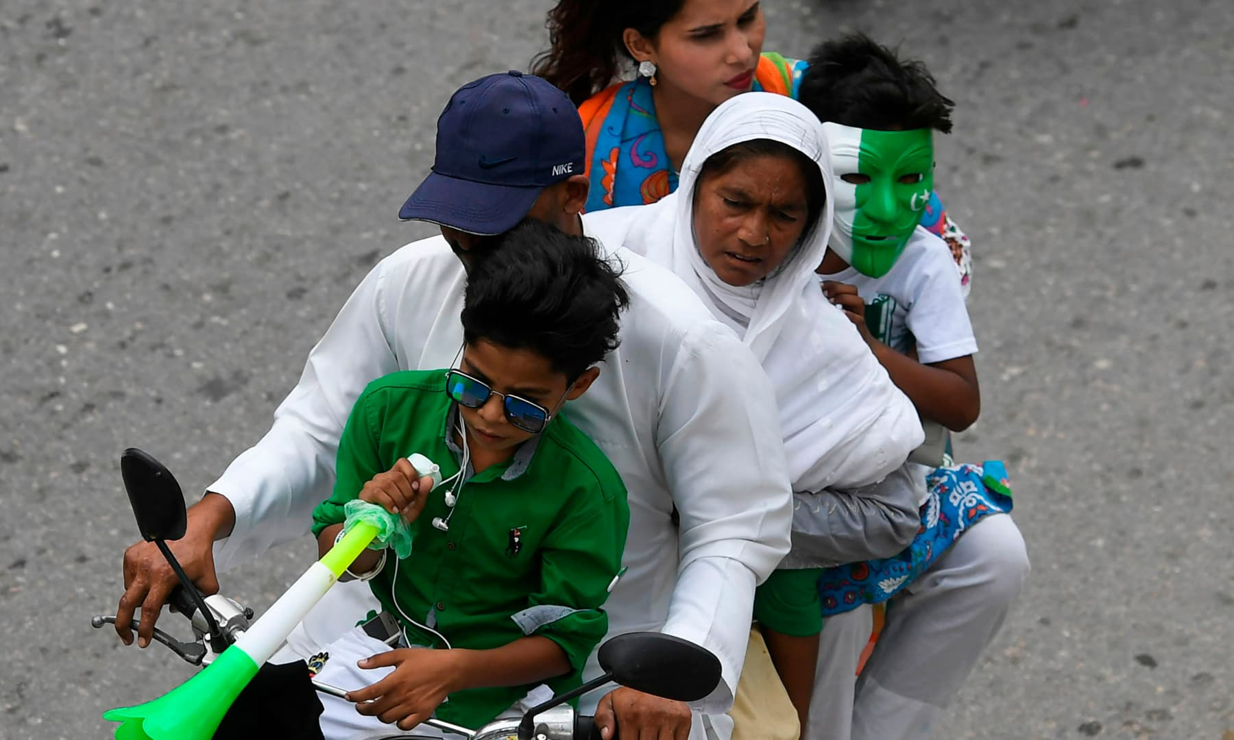 A family rides on a bike along a street during Independence Day celebrations in Islamabad on August 14. — AFP
