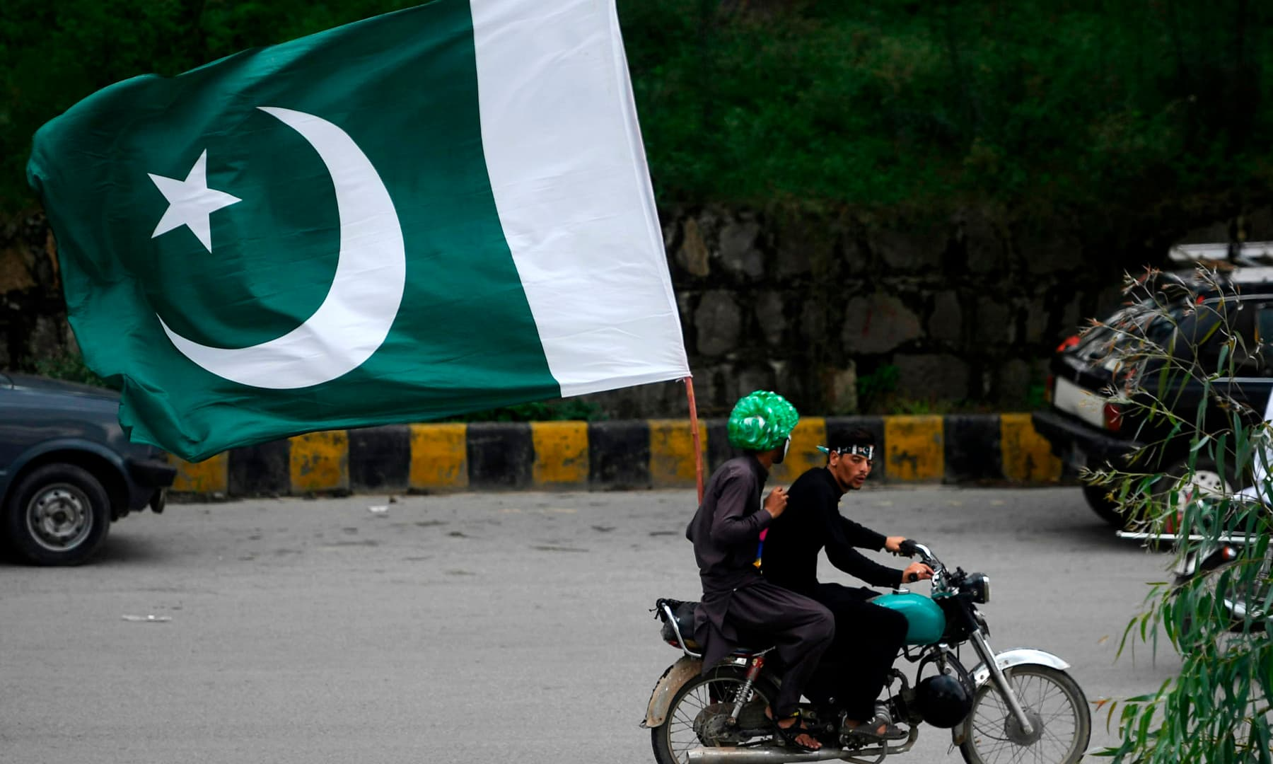 Men ride on a bike with a large flag of Pakistan along a street during Independence Day celebrations in Islamabad on August 14. — AFP