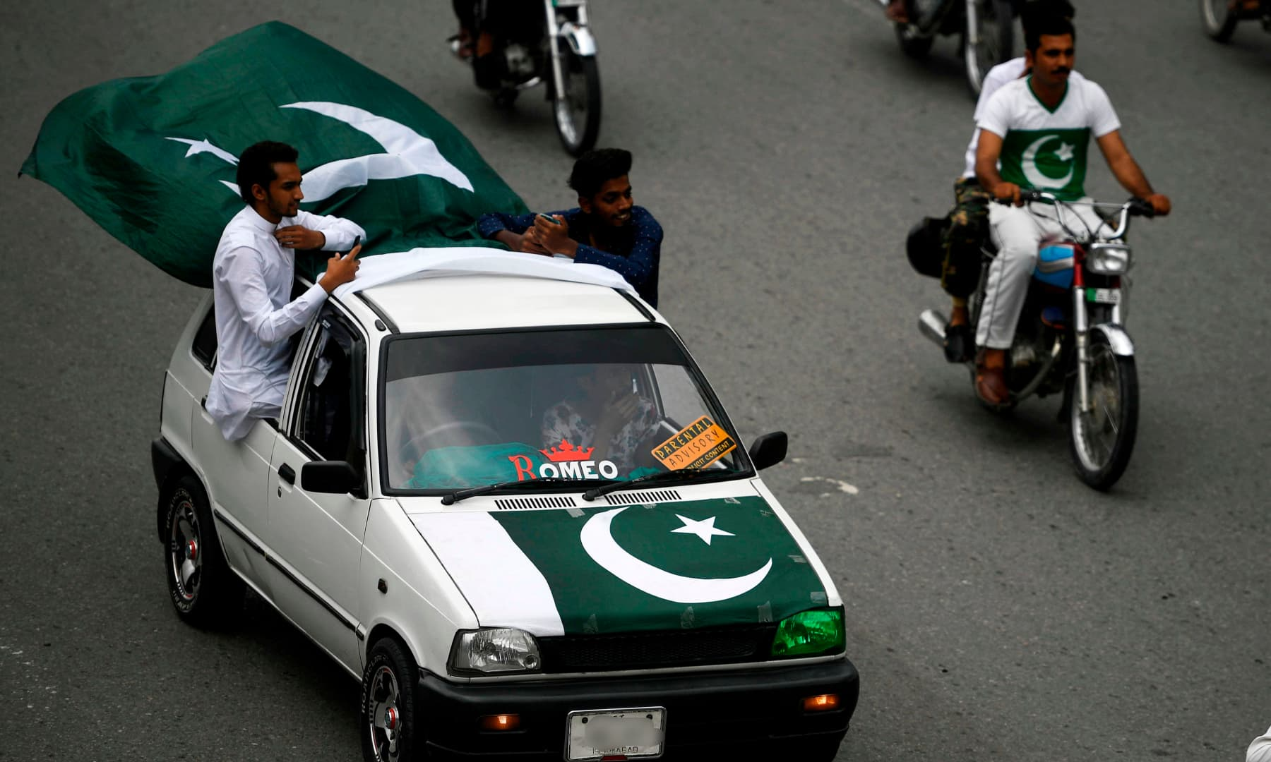 People drive along a street with national flags during Independence Day celebrations in Islamabad on August 14. — AFP