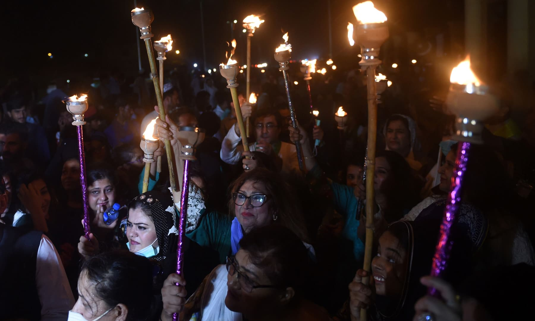 People hold torch lights during Independence Day celebrations in Karachi on August 14. — AFP