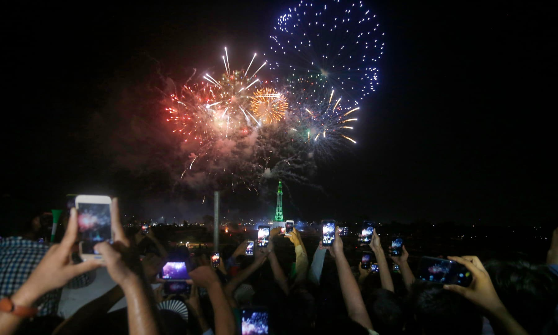 People use their mobile phones to film fireworks close to the Minar-e-Pakistan during Independence Day celebrations, in Lahore. — AP