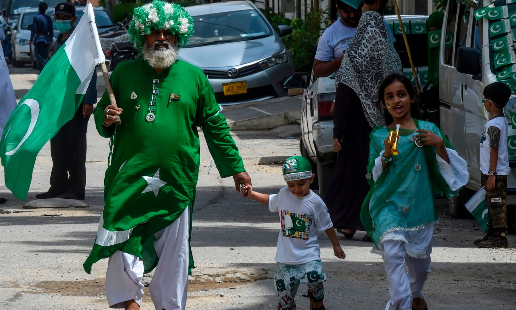 A man wearing an outfit designed as the Pakistani national flag walks along with his children in Karachi. — AFP