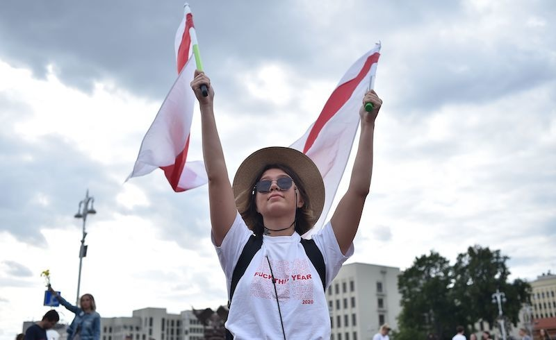 A woman holds two former white-red-white flags of Belarus used in opposition to the government during a protest rally against police violence during recent rallies of opposition supporters, who accuse strongman Alexander Lukashenko of falsifying the polls in the presidential election, in central Minsk on August 14, 2020. - Crowds of workers walked off the job on August 14, 2020, at several factories in Belarus's capital Minsk in support of the opposition calling for leader Alexander Lukashenko to step down. Hundreds of workers marched from the Minsk Automobile Plant (MAZ) and the Minsk Tractor