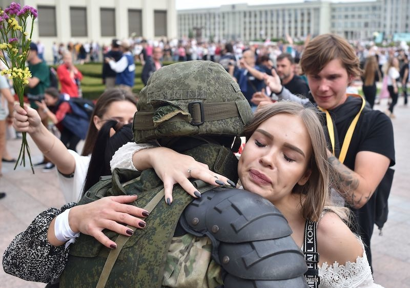 A woman hugs a Belarus' law enforcement officer during a protest rally against police violence during recent rallies of opposition supporters, who accuse strongman Alexander Lukashenko of falsifying the polls in the presidential election, in central Minsk on August 14, 2020. — AFP