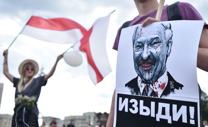 """A man holds a picture of the Belarus President Alexander Lukashenko reading """"Go away!"""" during a protest rally against police violence during recent rallies of opposition supporters, who accuse strongman Alexander Lukashenko of falsifying the polls in the presidential election, in central Minsk on August 14, 2020. — AFP"""