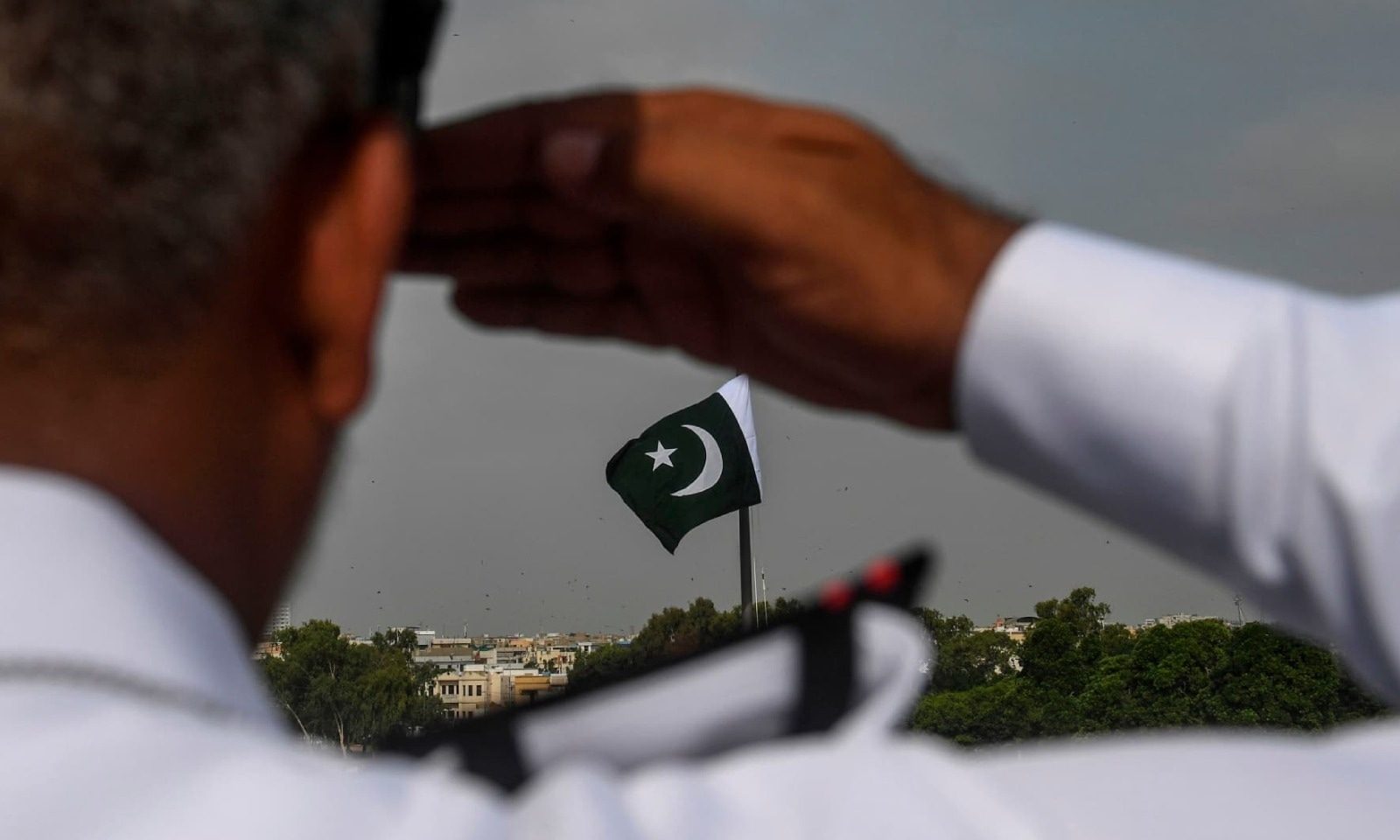 پاک بحریہ کے افسر قائد اعظم کی مزار پر لہرانے والے قومی پرچم کو سیلوٹ کر رہے ہیں — فوٹو: اے ایف پی