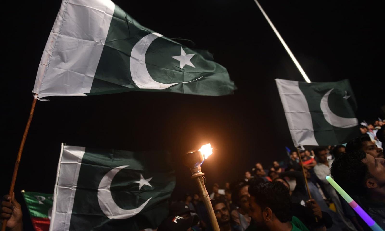 کراچی میں یوم آزادی کا جشن منانے والے لوگوں نے  قومی پرچم تھام رکھے ہیں — فوٹو: اے ایف پی